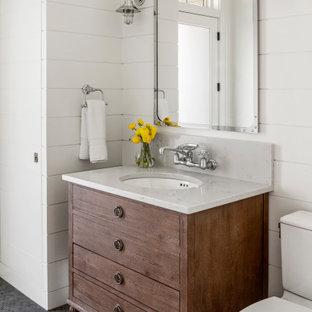 ボストンの中くらいのカントリー風おしゃれなトイレ・洗面所 (白い壁、珪岩の洗面台、グレーの洗面カウンター、家具調キャビネット、中間色木目調キャビネット、分離型トイレ、モザイクタイル、アンダーカウンター洗面器、黒い床、塗装板張りの壁) の写真
