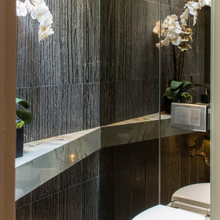 Small asian powder room in Los Angeles with a wall-mount toilet, gray tile, porcelain tile, grey walls, porcelain floors and grey floor.
