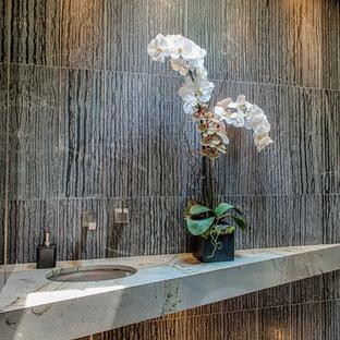 Réalisation d'un petit WC et toilettes design avec un WC suspendu, un carrelage gris, des carreaux de porcelaine, un mur gris, un sol en carrelage de porcelaine, un lavabo encastré, un plan de toilette en marbre et un sol gris.