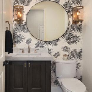 Cette photo montre un WC et toilettes chic avec un placard à porte shaker, des portes de placard noires, un WC séparé, un mur blanc, un sol en bois brun, un lavabo encastré, un plan de toilette en marbre, un sol marron et un plan de toilette multicolore.
