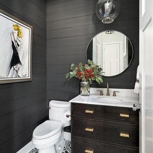 Cette image montre un WC et toilettes rustique avec un placard en trompe-l'oeil, des portes de placard en bois sombre, un WC à poser, un mur gris, un lavabo encastré et un sol multicolore.