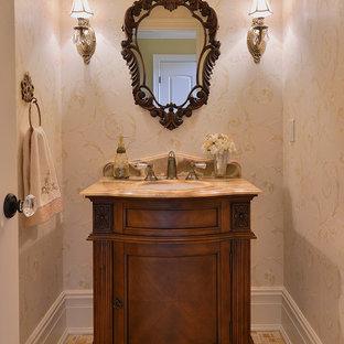 Cette image montre un petit WC et toilettes avec un lavabo encastré, un placard en trompe-l'oeil, des portes de placard en bois brun, un plan de toilette en onyx, un carrelage de pierre, un mur beige, un sol en carrelage de terre cuite et un carrelage beige.