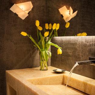 Cette image montre un grand WC et toilettes design avec un placard à porte plane, un carrelage gris, un lavabo intégré et un plan de toilette en onyx.