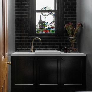 This is an example of a transitional powder room in Hobart with shaker cabinets, black cabinets, a drop-in sink, green floor and a built-in vanity.