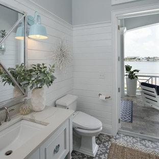 Idées déco pour un petit WC et toilettes bord de mer avec un placard avec porte à panneau encastré, des portes de placard blanches, un WC à poser, un mur gris, un sol en carrelage de céramique, un lavabo encastré, un plan de toilette en quartz, un sol multicolore et un plan de toilette blanc.