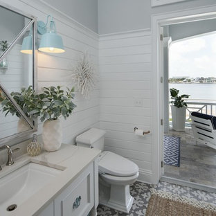 Inspiration for a small nautical cloakroom in Tampa with recessed-panel cabinets, white cabinets, a one-piece toilet, grey walls, ceramic flooring, a submerged sink, quartz worktops, multi-coloured floors and white worktops.