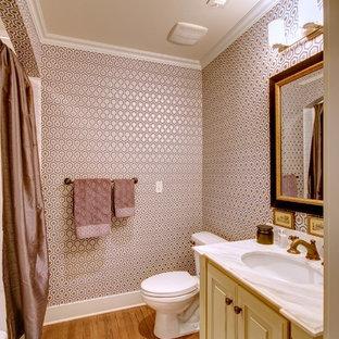 Неиссякаемый источник вдохновения для домашнего уюта: большой туалет в классическом стиле с врезной раковиной, фасадами с выступающей филенкой, мраморной столешницей, раздельным унитазом, белой плиткой, паркетным полом среднего тона и желтыми фасадами