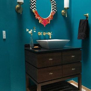Idée de décoration pour un WC et toilettes minimaliste de taille moyenne avec un placard en trompe-l'oeil, des portes de placard en bois brun, un WC séparé, un carrelage gris, un mur bleu, une vasque, un plan de toilette en granite et un sol en carreaux de ciment.