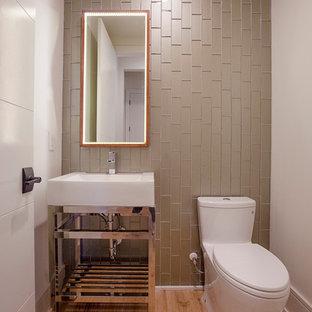 Стильный дизайн: туалет среднего размера в современном стиле с открытыми фасадами, унитазом-моноблоком, бежевой плиткой, зеленой плиткой, стеклянной плиткой, серыми стенами, паркетным полом среднего тона и монолитной раковиной - последний тренд