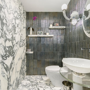 This is an example of an eclectic cloakroom in New York with glass-front cabinets, a one-piece toilet, multi-coloured tiles, stone slabs, multi-coloured walls, marble flooring, a pedestal sink, glass worktops and multi-coloured floors.