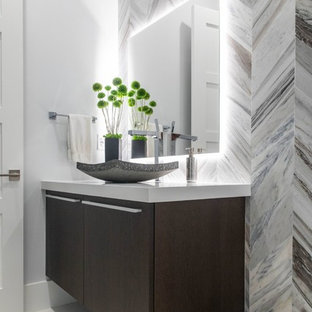 Inspiration for a mid-sized contemporary gray tile and marble tile porcelain floor and white floor powder room remodel in Miami with flat-panel cabinets, dark wood cabinets, a one-piece toilet, blue walls, a vessel sink, quartz countertops and white countertops