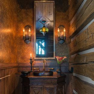 Idéer för att renovera ett rustikt brun brunt toalett, med möbel-liknande, skåp i mörkt trä, bruna väggar, ett fristående handfat och träbänkskiva