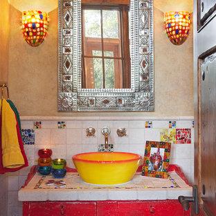 Неиссякаемый источник вдохновения для домашнего уюта: туалет в стиле фьюжн с настольной раковиной, столешницей из плитки, красными фасадами, керамической плиткой, бежевыми стенами, фасадами с утопленной филенкой и белой столешницей