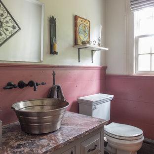 Стильный дизайн: маленький туалет в стиле кантри с настольной раковиной, мраморной столешницей, серыми фасадами, розовыми стенами, паркетным полом среднего тона, раздельным унитазом и фасадами с выступающей филенкой - последний тренд