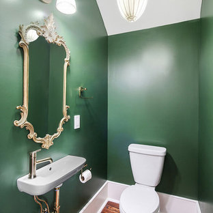 Foto de aseo clásico, pequeño, con paredes verdes, suelo de madera en tonos medios, lavabo suspendido, suelo marrón y sanitario de dos piezas