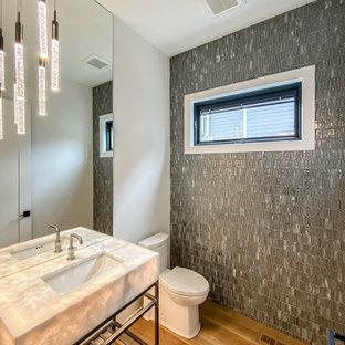 Immagine di un grande bagno di servizio industriale con WC monopezzo, piastrelle grigie, piastrelle di vetro, pareti bianche, parquet chiaro, lavabo da incasso, top in quarzite, top bianco e mobile bagno freestanding