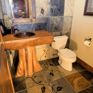 Medium sized classic cloakroom in Seattle with a built-in sink, freestanding cabinets, medium wood cabinets, wooden worktops, a two-piece toilet, brown tiles, beige walls, slate flooring and stone tiles.