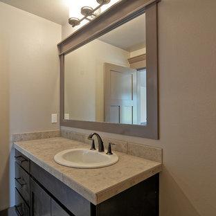 Ejemplo de aseo de estilo americano, de tamaño medio, con armarios con paneles lisos, puertas de armario de madera en tonos medios, sanitario de pared, baldosas y/o azulejos beige, baldosas y/o azulejos de piedra, paredes beige, lavabo encastrado, encimera de azulejos y encimeras grises