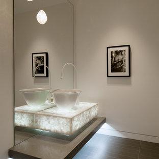 На фото: туалет среднего размера в современном стиле с открытыми фасадами, серыми фасадами, бежевыми стенами, полом из винила, настольной раковиной, столешницей из бетона, черным полом и серой столешницей с