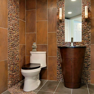 Photo of a small traditional cloakroom in San Francisco with a submerged sink, flat-panel cabinets, dark wood cabinets, engineered stone worktops, a one-piece toilet, multi-coloured tiles, pebble tiles, brown walls and porcelain flooring.