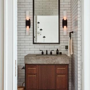 Klassische Gästetoilette mit flächenbündigen Schrankfronten, dunklen Holzschränken, weißen Fliesen, Unterbauwaschbecken, grauem Boden und grauer Waschtischplatte in Philadelphia