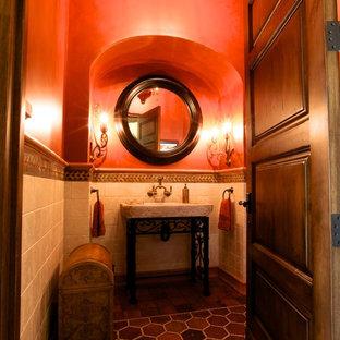 Idées déco pour un WC et toilettes victorien de taille moyenne avec un placard en trompe-l'oeil, un carrelage beige, du carrelage en travertin, un mur rouge, un sol en carreau de terre cuite, une grande vasque et un sol rouge.