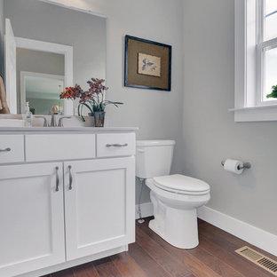 Diseño de aseo de estilo americano, grande, con puertas de armario blancas, sanitario de dos piezas, paredes beige, suelo de madera en tonos medios, lavabo integrado y encimera de mármol
