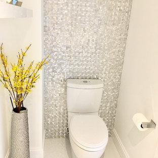 Foto på ett litet funkis toalett, med släta luckor, vita skåp, en toalettstol med separat cisternkåpa, vit kakel, kakel i metall, vita väggar, klinkergolv i porslin, ett integrerad handfat, bänkskiva i kvartsit och vitt golv