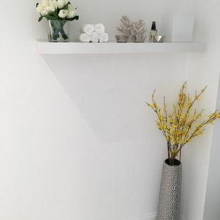 Modern inredning av ett litet toalett, med släta luckor, vita skåp, en toalettstol med hel cisternkåpa, flerfärgad kakel, kakel i metall, vita väggar, klinkergolv i porslin, ett integrerad handfat, bänkskiva i kvartsit och vitt golv