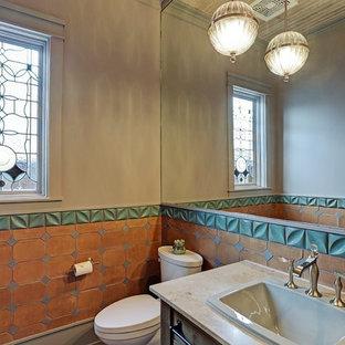 Ispirazione per un bagno di servizio minimal di medie dimensioni con WC a due pezzi, piastrelle marroni, piastrelle multicolore, piastrelle in terracotta, pareti beige, lavabo da incasso, top in granito e top beige