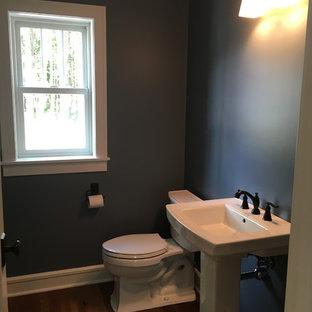 Exemple d'un WC et toilettes craftsman de taille moyenne avec un WC séparé, un mur bleu, un sol en bois foncé et un lavabo de ferme.