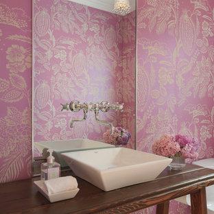 プロビデンスのカントリー風おしゃれなトイレ・洗面所 (ベッセル式洗面器、木製洗面台、ピンクの壁、ブラウンの洗面カウンター) の写真