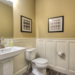 На фото: туалет в классическом стиле с раковиной с пьедесталом, раздельным унитазом, бежевыми стенами и полом из линолеума с