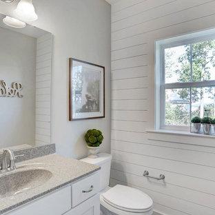 他の地域の広いおしゃれなトイレ・洗面所 (黄色いキャビネット、分離型トイレ、ベージュの壁、一体型シンク、御影石の洗面台) の写真