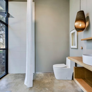 Inspiration for an industrial white tile concrete floor and gray floor powder room remodel in Austin with open cabinets, light wood cabinets, a one-piece toilet, gray walls, a vessel sink, wood countertops and brown countertops