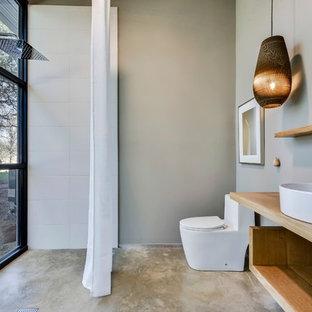 Стильный дизайн: туалет в стиле лофт с открытыми фасадами, светлыми деревянными фасадами, унитазом-моноблоком, белой плиткой, серыми стенами, бетонным полом, настольной раковиной, столешницей из дерева, коричневой столешницей и серым полом - последний тренд