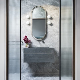Contemporary powder room in Sydney with flat-panel cabinets, grey cabinets, gray tile, grey walls, an integrated sink, grey floor and grey benchtops.