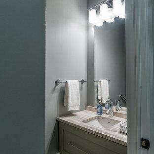 Modelo de aseo tradicional renovado, pequeño, con lavabo bajoencimera, armarios estilo shaker, puertas de armario grises, encimera de mármol, sanitario de una pieza, paredes grises y suelo de madera oscura