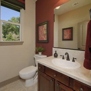 Ispirazione per un bagno di servizio tradizionale di medie dimensioni con ante con bugna sagomata, WC a due pezzi, piastrelle beige, piastrelle di pietra calcarea, pareti beige, pavimento in pietra calcarea, lavabo sottopiano, top in pietra calcarea, pavimento beige e top beige