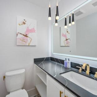 ヒューストンの中くらいのモダンスタイルのおしゃれなトイレ・洗面所 (レイズドパネル扉のキャビネット、白いキャビネット、分離型トイレ、グレーの壁、大理石の床、アンダーカウンター洗面器、人工大理石カウンター、紫の床、黒い洗面カウンター) の写真
