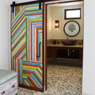 Cette photo montre un WC et toilettes éclectique de taille moyenne avec un placard à porte plane, des portes de placard en bois sombre, un WC à poser, un mur beige, un sol en galet et une vasque.
