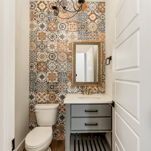 Country cloakroom in Other with flat-panel cabinets, grey cabinets, a two-piece toilet, multi-coloured tiles, white walls, medium hardwood flooring, a submerged sink, brown floors and white worktops.