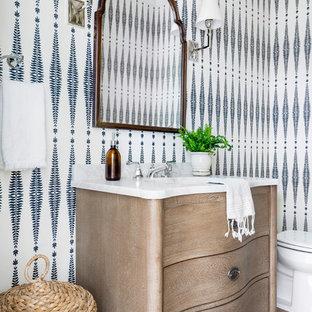 Kleine Maritime Gästetoilette mit verzierten Schränken, Marmor-Waschbecken/Waschtisch, braunem Boden, weißer Waschtischplatte, hellbraunen Holzschränken, weißer Wandfarbe, braunem Holzboden und Unterbauwaschbecken in Minneapolis