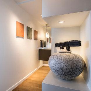 Kleine Moderne Gästetoilette mit Glasfronten, grauen Schränken, beiger Wandfarbe, braunem Holzboden, integriertem Waschbecken, Glaswaschbecken/Glaswaschtisch und beigem Boden in Phoenix