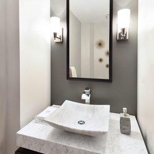 Kleine Moderne Gästetoilette mit flächenbündigen Schrankfronten, grauer Wandfarbe, Aufsatzwaschbecken, Marmor-Waschbecken/Waschtisch, dunklen Holzschränken, Toilette mit Aufsatzspülkasten, grauen Fliesen, Zementfliesen, braunem Holzboden und weißer Waschtischplatte in Atlanta