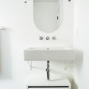 Kleine Nordische Gästetoilette mit weißer Wandfarbe, Porzellan-Bodenfliesen, Wandwaschbecken, grünem Boden, flächenbündigen Schrankfronten und weißen Schränken in Salt Lake City