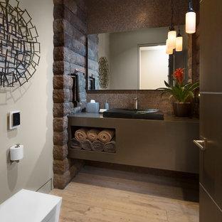 Cette image montre un WC et toilettes design de taille moyenne avec des portes de placard grises, un carrelage marron, carrelage en mosaïque, un mur gris, un sol en bois clair, une vasque, un plan de toilette en stratifié, un placard sans porte et un sol beige.