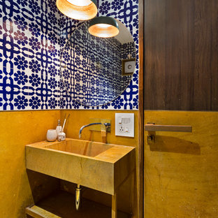 Inspiration for a small contemporary cloakroom in Mumbai with open cabinets, multi-coloured walls, an integrated sink and yellow floors.