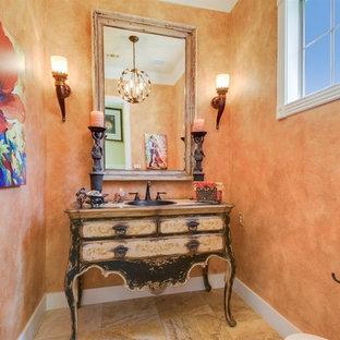 Cette photo montre un petit WC et toilettes méditerranéen avec un placard en trompe-l'oeil, un mur orange, un sol en carrelage de céramique et un sol beige.
