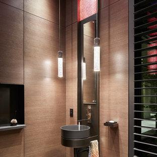 Modelo de aseo contemporáneo con paredes marrones y lavabo sobreencimera